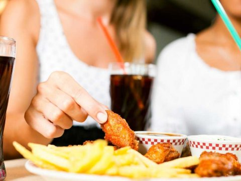 women-eating-chicken-wings-restaurant-soda
